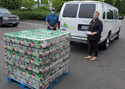 Two people wearing pandemic masks with a pallet of tuna cans